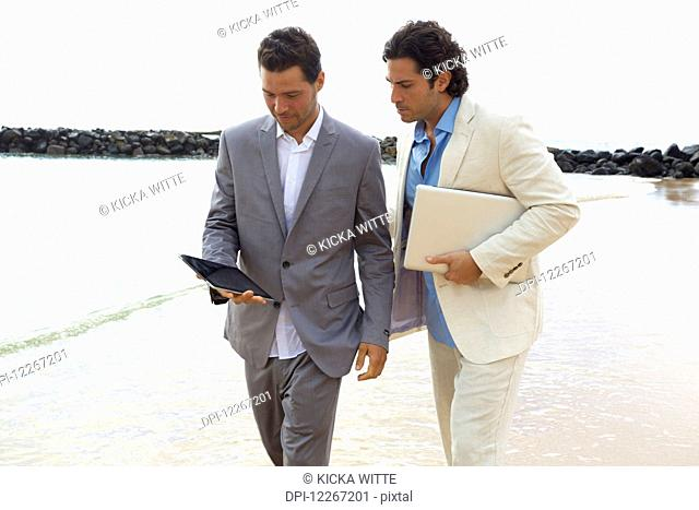 Businessmen walking with tablet and laptop at the water's edge, Lydgate Beach; Kauai, Hawaii, United States of America