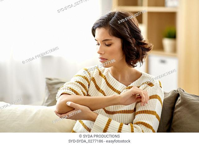 unhappy woman suffering from pain in hand at home