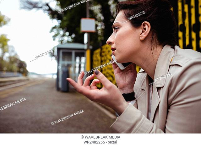 Woman talking on phone at railroad station