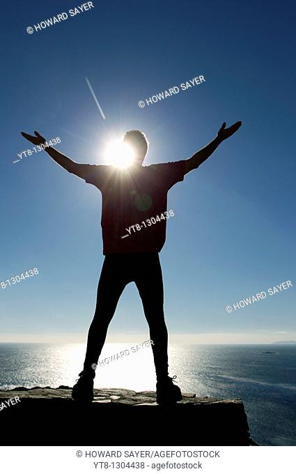 Silhouette of a male athlete by the sea reaching up to the sky