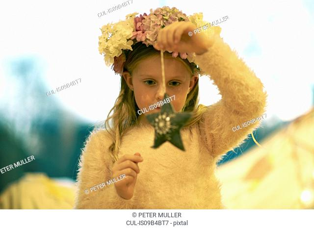 Girl with flowers in her hair holding and gazing at star decoration