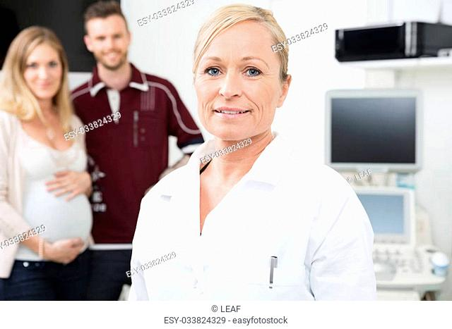 Portrait of mid adult female obstetrician with expectant couple standing in background