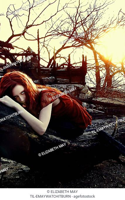 A girl laying on a fallen, burned tree amid a rubble from a burned house as the sun sets behind her