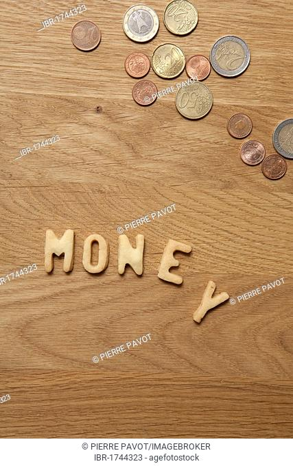 Money, word written with biscuits, beside coins