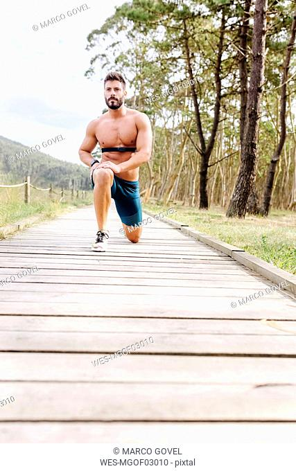 Barechested man exercising on boardwalk