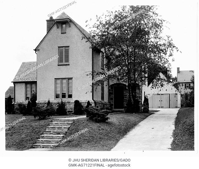 Landscape shot of a large white three-story house with steps leading to the entrance of the house, a wide white path leads to a shed behind the house