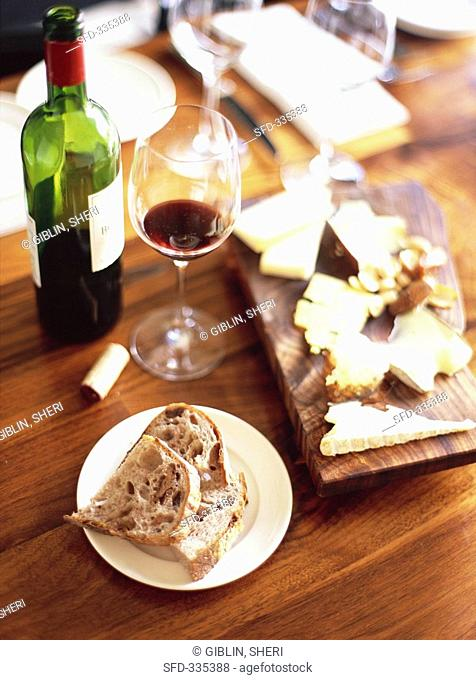 Red wine, bread and cheese board on table