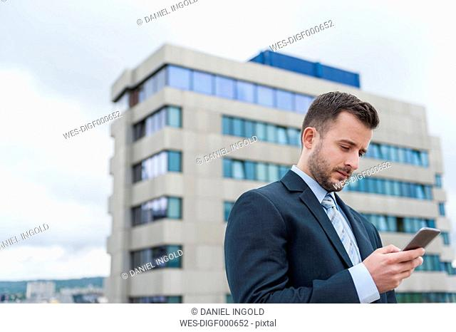 Businessman looking at cell phone in front of office building
