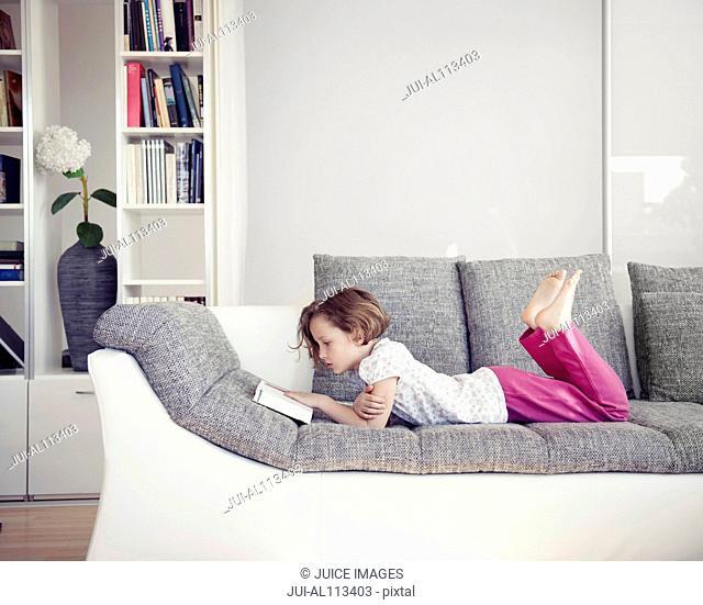 Young girl lying on sofa reading