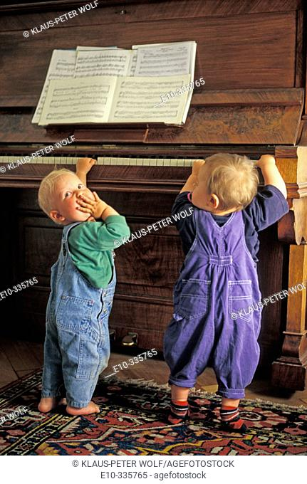 Two 11 month old boys playing the piano