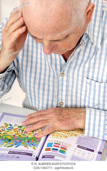 Senior man reading a book and exercising his memory withs tests to prevent Alzheimer disease