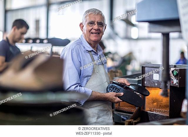 Smiling shoemaker working on shoe in workshop