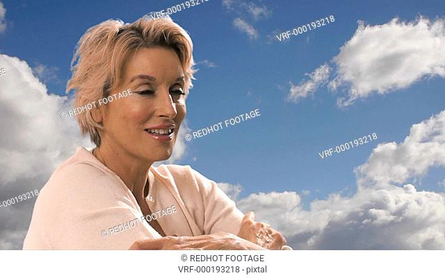 Dolly shot of woman sitting with blue sky and clouds in background