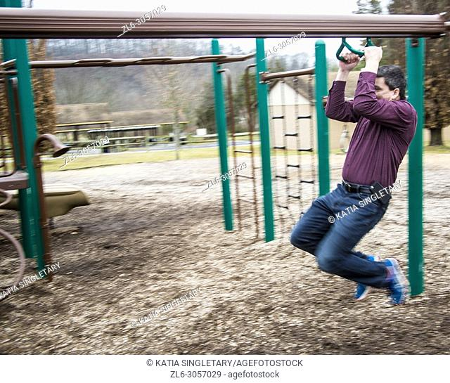 Caucasian handsome dark hair man wearing a purple shirt and his bluetooth. He is in playing in kids playground and going down the Zipline