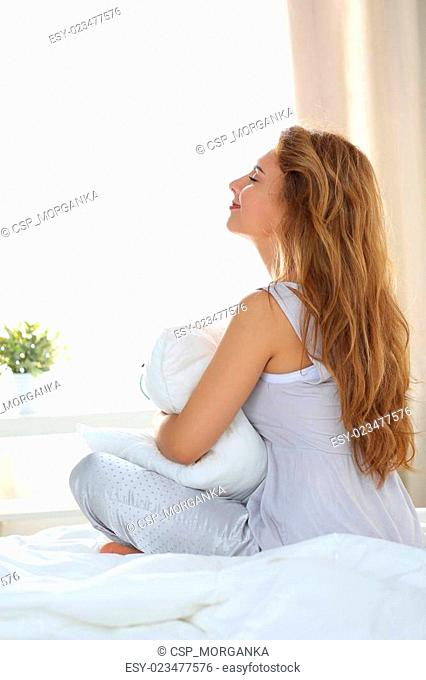 Young beautiful woman wearing pyjamas sitting on her bed holding her pillow