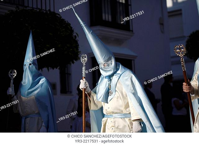 Hooded penitents holding staffs participate on the procession of Palm Sunday during Easter Week in Prado del Rey, Sierra de Grazalema Natural Park