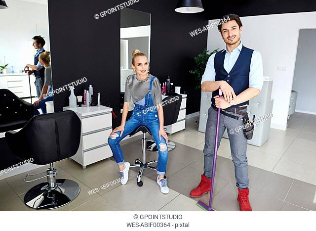 Portrait of confident hairdresser and woman in hair salon
