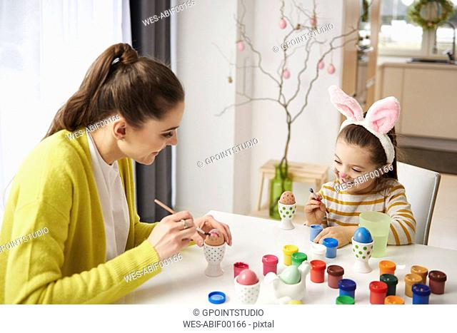 Happy mother and daughter with bunny ears sitting at table painting Easter eggs