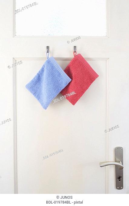 two washcloths hanging on bathroom door