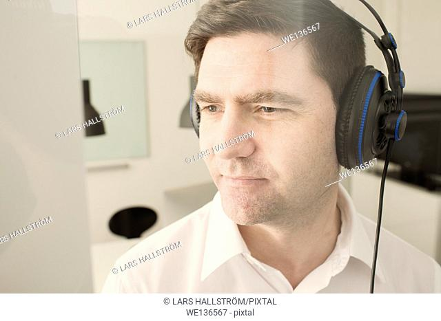 Man with headphones in office listening to music