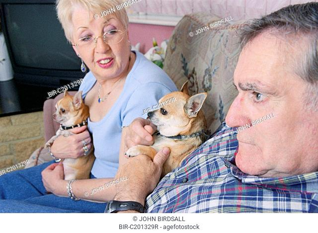 Man with Alzheimer's disease sitting on sofa with wife and pet dogs