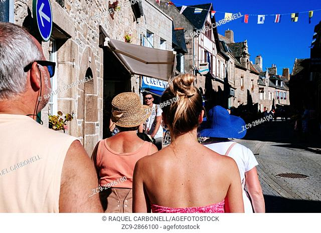 Tourists walking on street full of traditional fifteenth-century stone houses. Morlaix, Brittany, France