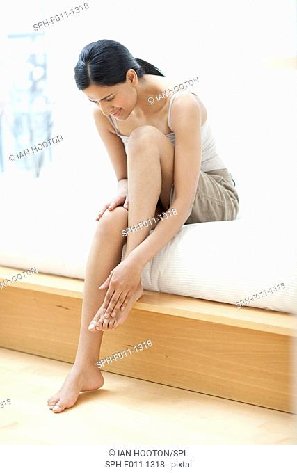 Young woman touching her foot