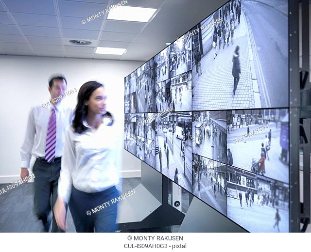 Security workers walking past CCTV screens in control room