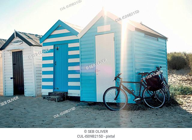 Bicycle leaning against row of beach huts, Southwold, Suffolk, UK