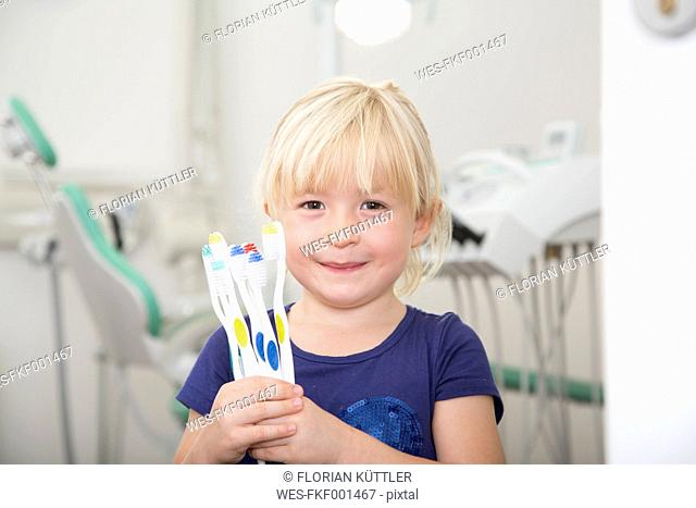 Girl in dental sugery holding toothbrushes
