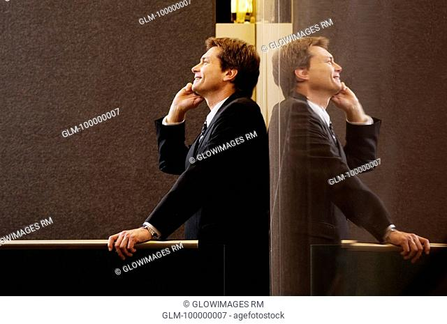 Side profile of a businessman talking on a mobile phone and smiling