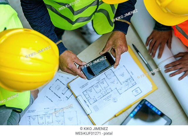 Woman and two men in workwear taking cell phone picture of a construction plan