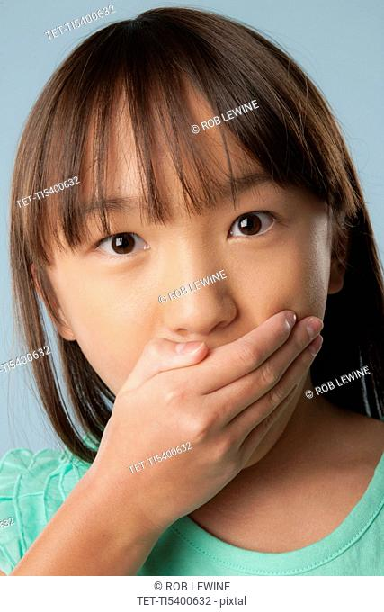 Studio shot of girl 10-11 covering mouth with hand
