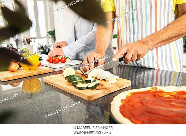 Couple cutting vegetables in the kitchen