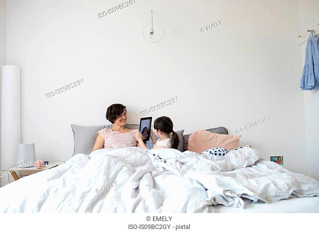 Mother and daughter relaxing in bed, daughter photographing mother using digital tablet