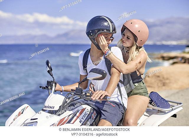 Greece, Crete, Chersonissos, couple driving quad next to coast, girlfriend fixing sunglasses of boyfriend