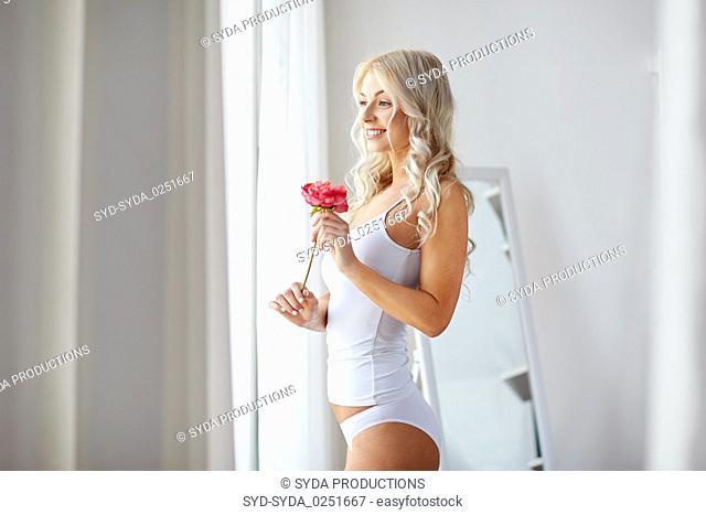 woman in underwear smelling flower at window