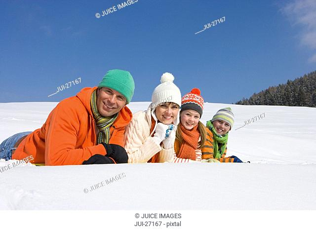 Smiling family laying in snow together