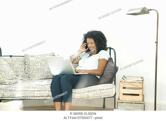 Woman chatting on cell phone and using laptop computer at home