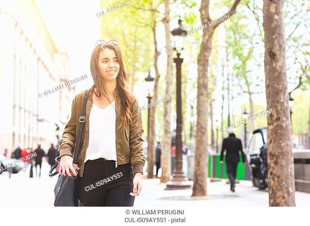 Young woman strolling along sidewalk, Paris, France