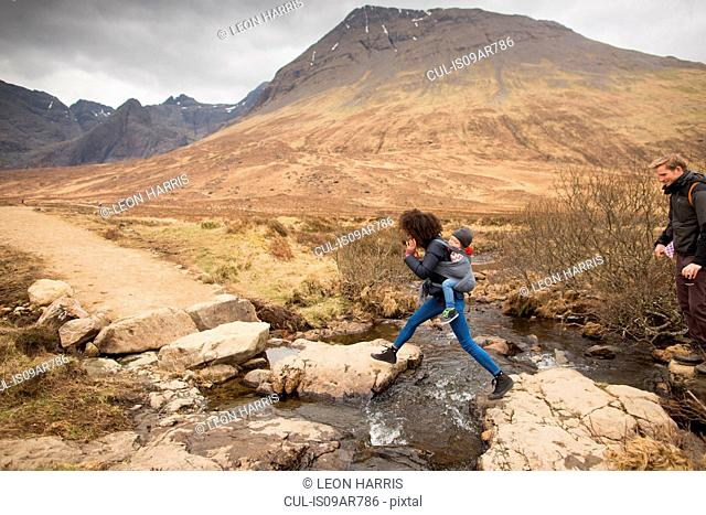 Woman leaping over stream, Fairy Pools, near Glenbrittle, Isle of Skye, Hebrides, Scotland
