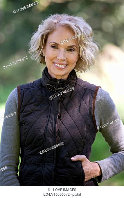 A portrait of a mature woman standing outdoors, smiling