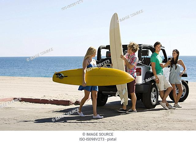 Friends by vehicle with surfboards