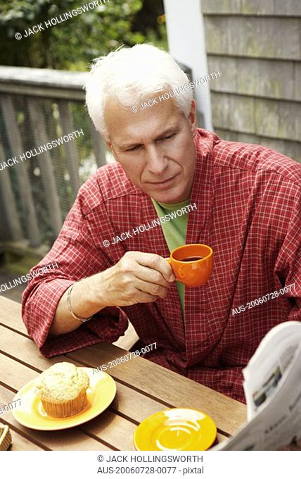 Close-up of a mature man sitting at the table and holding a cup of black tea