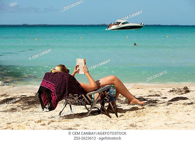 Tourist woman reading a book and relaxing near the sea, Isla Mujeres, Cancun, Quintana Roo, Yucatan Province, Mexico, North America