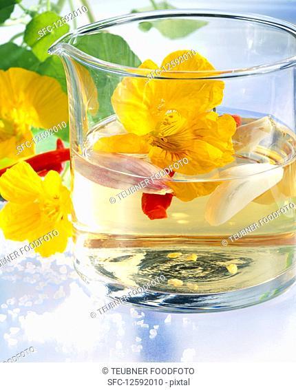 Homemade vinegar with nasturtium flowers, garlic, shallots, chilis, salt and white wine vinegar