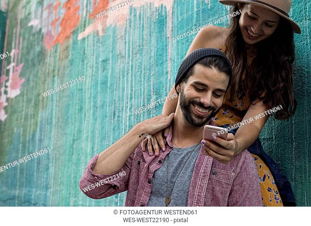 Happy young couple with cell phone outdoors
