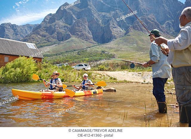 Active senior friends fishing and kayaking at sunny summer lake
