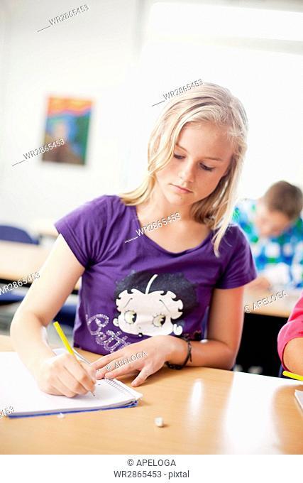 Girl writing on book in classroom
