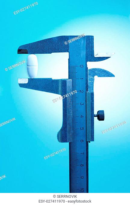 Caliper measures size of white pill, on blue